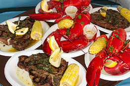 Plates of steak, corn and lobster