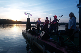 View of a band performing on the lake pier with the sun setting behind them