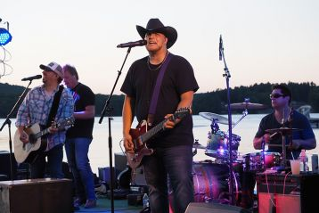 Man in black shirt and black cowboy hat playing guitar and singing onstage with a band